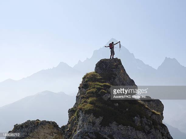 Mountaineer raises arms & rope on mountain summit