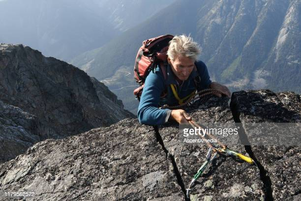 mountaineer rappels himself off cliff - ascent xmedia stock pictures, royalty-free photos & images