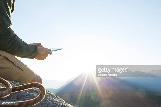 Mountaineer relaxes on rock ledge,uses tablet