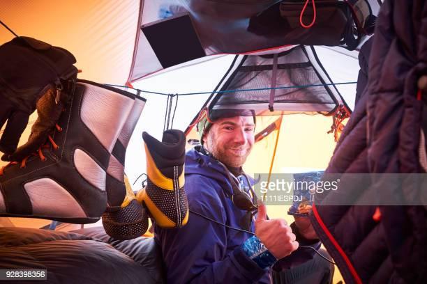 Bergbeklimmer zitten in de ingang van een tent.