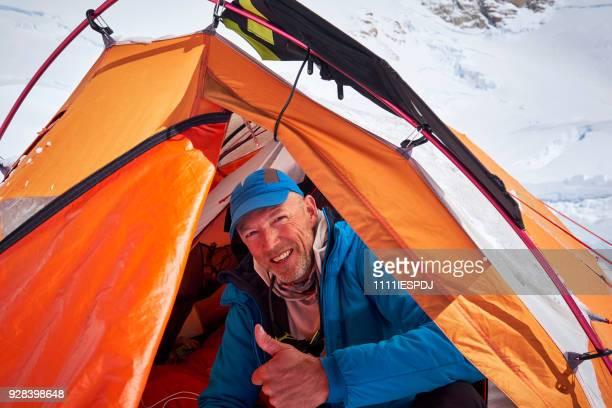 Bergbeklimmer zitten in de ingang van een tent