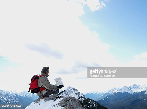 Mountaineer sitting on mountain top, holding map
