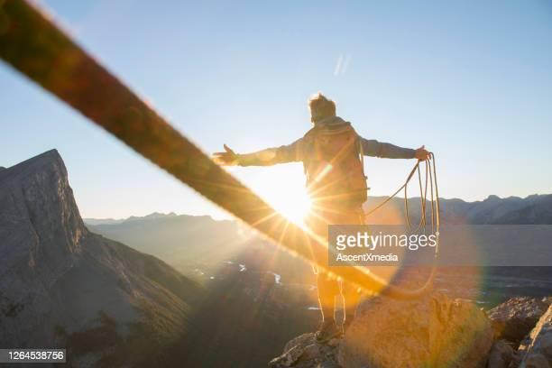 alpinista allarga le braccia per festeggiare sulla vetta della montagna - motivazione foto e immagini stock