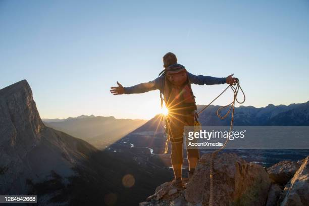 mountaineer spreads arms to celebrate on mountain summit - brightly lit stock pictures, royalty-free photos & images