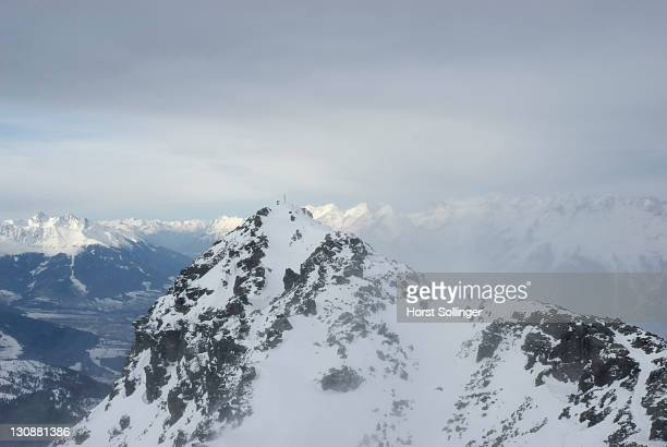 Mountaineer standing next to landmark cross on snow covered alpine peak above the Inn valley during Foehn storm, Tyrol Austria