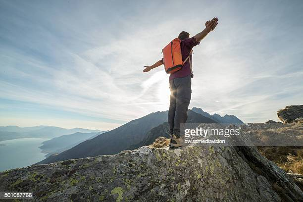 Mountaineer stands arms outstretched on mountain top