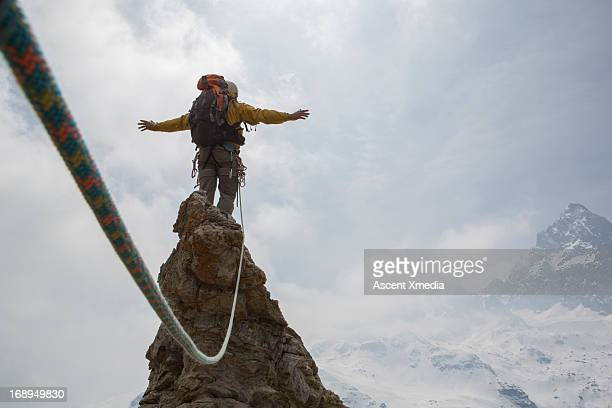 mountaineer stands on summit, arms outstretched - hero and not superhero stock pictures, royalty-free photos & images