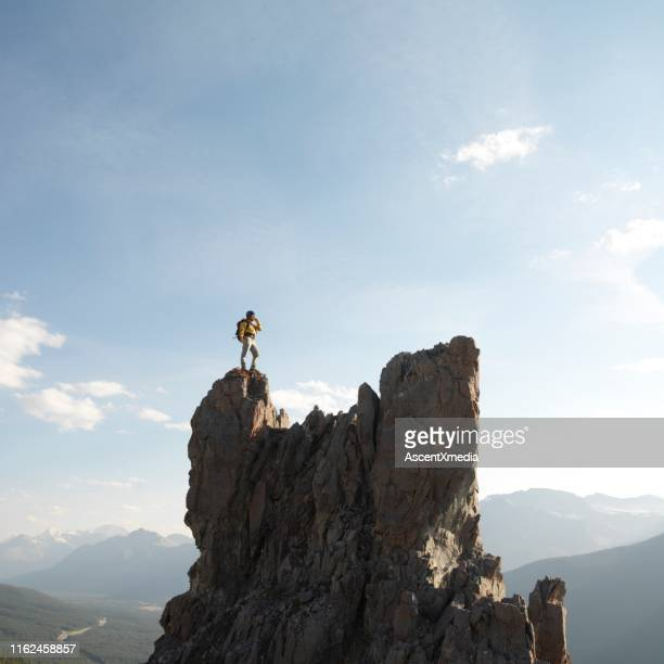 mountaineer stands on summit of pinnacle - ascent xmedia stock pictures, royalty-free photos & images