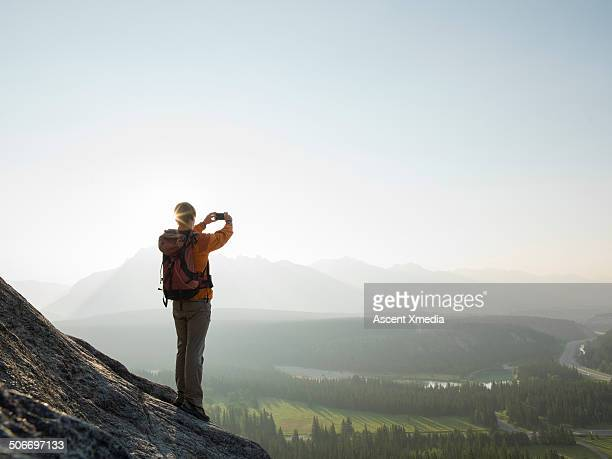 Mountaineer takes picture across mountain valley