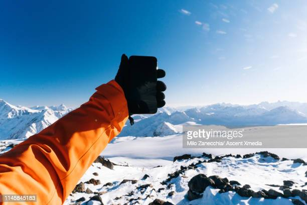 mountaineer takes selfie on summit - sports glove stock pictures, royalty-free photos & images
