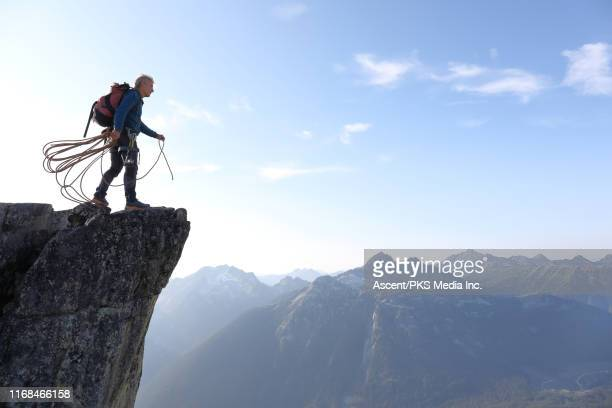 mountaineer throws out rope for rappel (abseil) - early retirement stock pictures, royalty-free photos & images