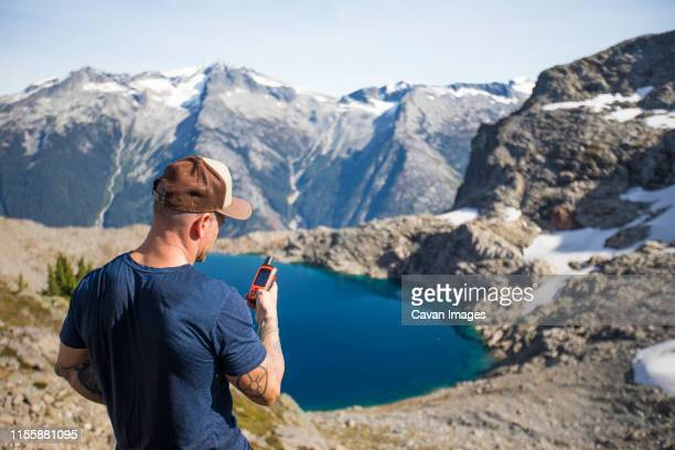 mountaineer views the climbing route using a gps device. - sos ストックフォトと画像