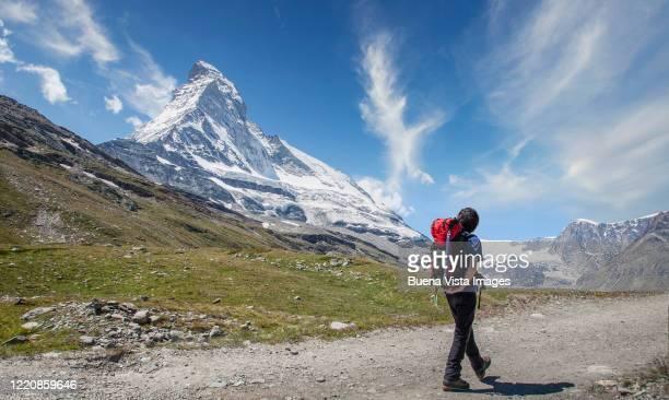 mountaineer walking under matterhorn - monte cervino foto e immagini stock