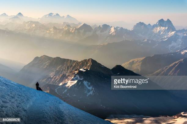 Mountaineer walking up to the summit of Mt.Elbrus, Russia with Caucasus in background