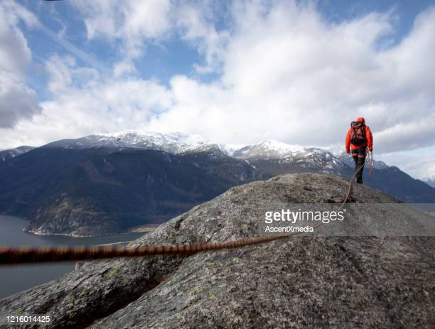mountaineer walks along mountain ridge with climbing rope - direction stock pictures, royalty-free photos & images