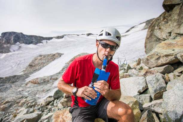 Mountaineer water from bottle with a filter attached.