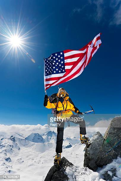 Mountaineer waving US flag on mountain peak