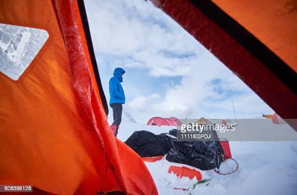 Alpinisme man staat buiten zijn tent.