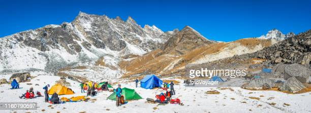 mountaineering team setting up camp in himalaya mountains panorama nepal - base camp stock pictures, royalty-free photos & images