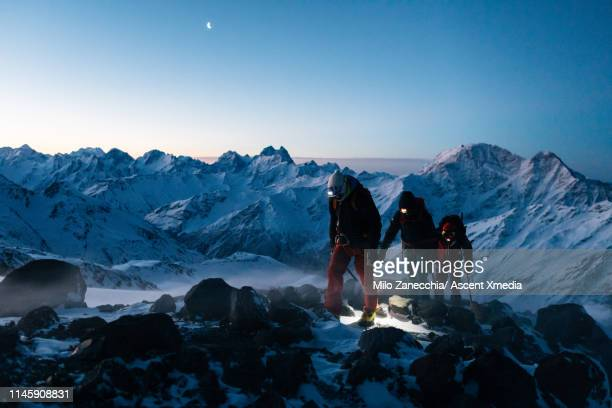 mountaineers advance towards mountain summit in the twilight - ascent xmedia stock pictures, royalty-free photos & images