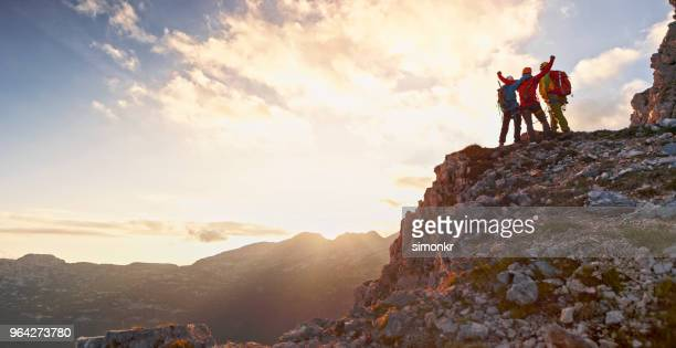 mountaineers celebrating victory - mountain peak stock pictures, royalty-free photos & images