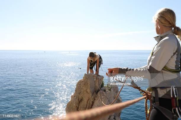 bergsteiger klettern über das mittelmeer - sicherheitsausrüstung stock-fotos und bilder