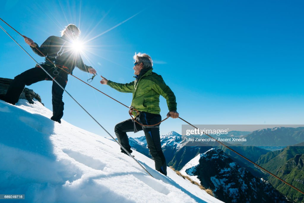 Mountaineers climb along rope, exchange gear : Stock Photo