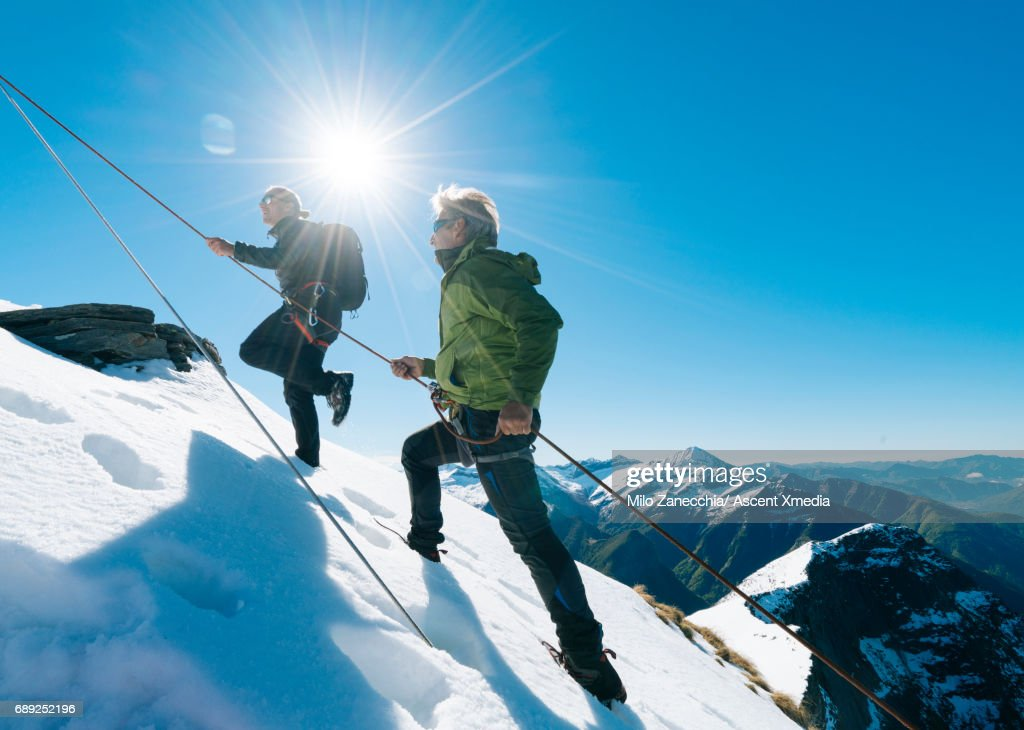 Mountaineers climb along rope to mountain summit : Foto de stock