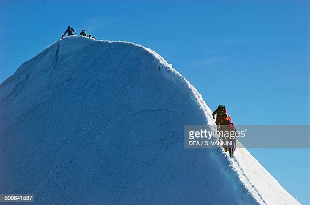 Mountaineers climbing the ridge to the summit of Castor Monte Rosa massif Aosta Valley Italy