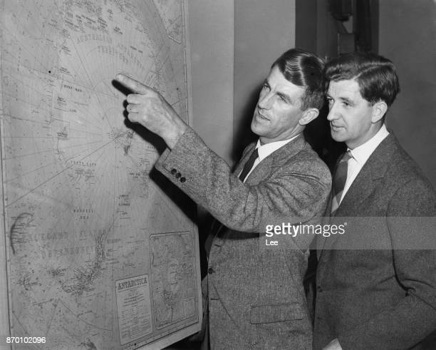 Mountaineers Edmund Hillary and George Lowe study a map of the land route across Antarctica during a press conference at the Royal Geographical...