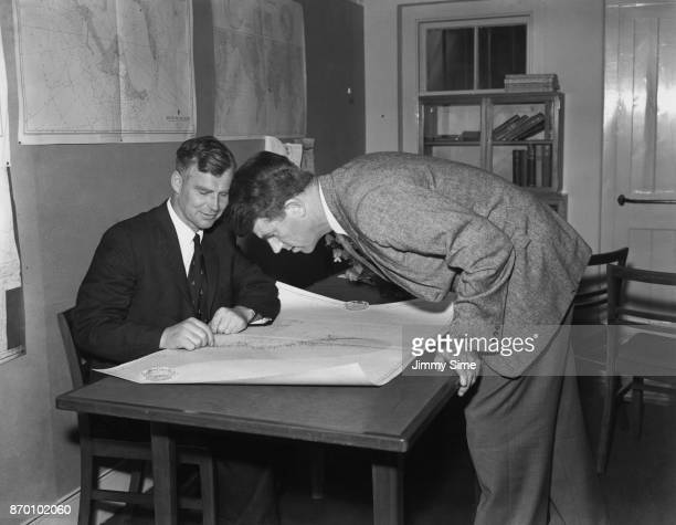 Mountaineers Edmund Hillary and Vivian Fuchs study a map of the land route across Antarctica in London 21st July 1955 They are both to take part in...
