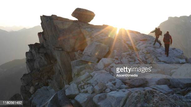 mountaineers hike along rocky summit at sunrise - ascent xmedia stock pictures, royalty-free photos & images