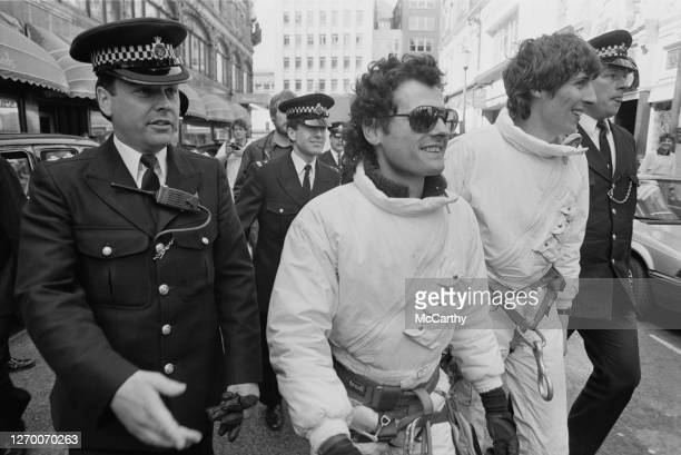 Mountaineers Joe Simpson and John Stevenson of Greenpeace are escorted away by police after staging a demonstration against the sale of fur at...
