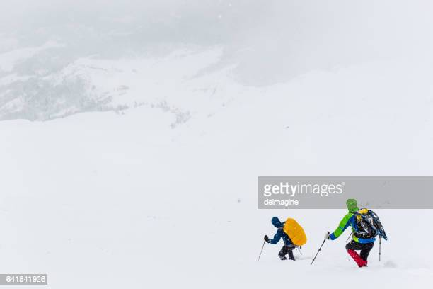 alpinisti su sentiero innevato durante tempesta di neve - clima alpino foto e immagini stock
