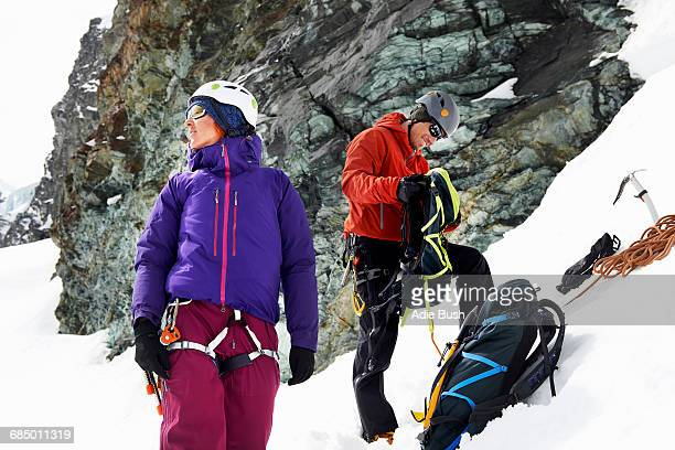 Mountaineers preparing equipment on snow-covered mountain, Saas Fee, Switzerland