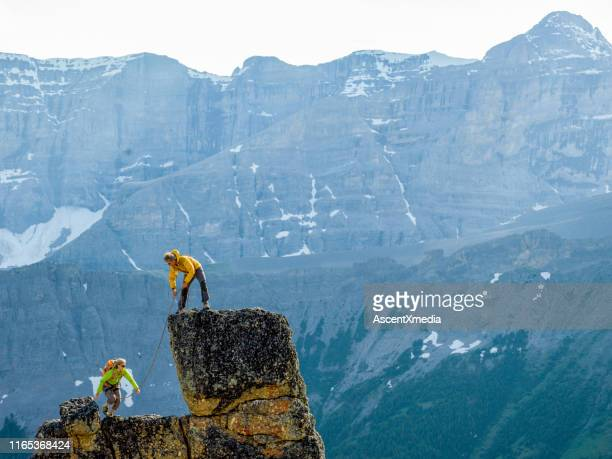 mountaineers scale rocks steps on cliff with rope - ascent xmedia stock pictures, royalty-free photos & images