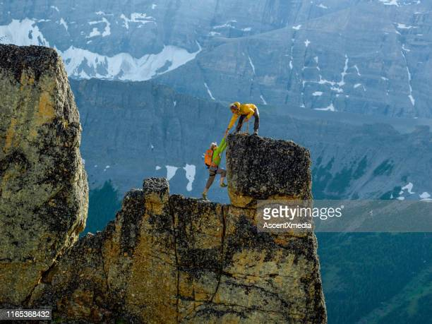 mountaineers scale rocks steps on cliff with rope - climbing stock pictures, royalty-free photos & images