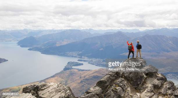 Mountaineers stand on mountain summit, take selfie