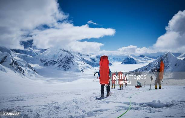 mountaineers with sledge on his back coming down on denali. - mt mckinley stock photos and pictures