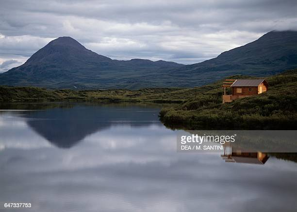 Mountains and a farmhouse reflected in the waters of a lake Glenn Highway Alaska United States of America