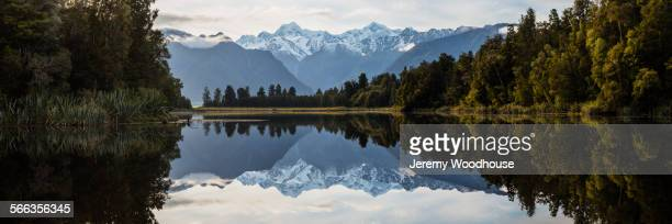 Mountains and forest reflecting in still lake, Mt Cook Village, South Westland, New Zealand