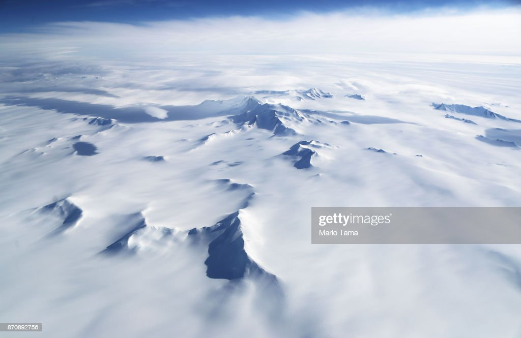 Mountains and land ice are seen from NASA's Operation IceBridge research aircraft in the Antarctic Peninsula region, on November 4, 2017, above Antarctica. NASA's Operation IceBridge has been studying how polar ice has evolved over the past nine years and is currently flying a set of nine-hour research flights over West Antarctica to monitor ice loss aboard a retrofitted 1966 Lockheed P-3 aircraft. According to NASA, the current mission targets 'sea ice in the Bellingshausen and Weddell seas and glaciers in the Antarctic Peninsula and along the English and Bryan Coasts.' Researchers have used the IceBridge data to observe that the West Antarctic Ice Sheet may be in a state of irreversible decline directly contributing to rising sea levels. The National Climate Assessment, a study produced every 4 years by scientists from 13 federal agencies of the U.S. government, released a stark report November 2 stating that global temperature rise over the past 115 years has been primarily caused by 'human activities, especially emissions of greenhouse gases'.