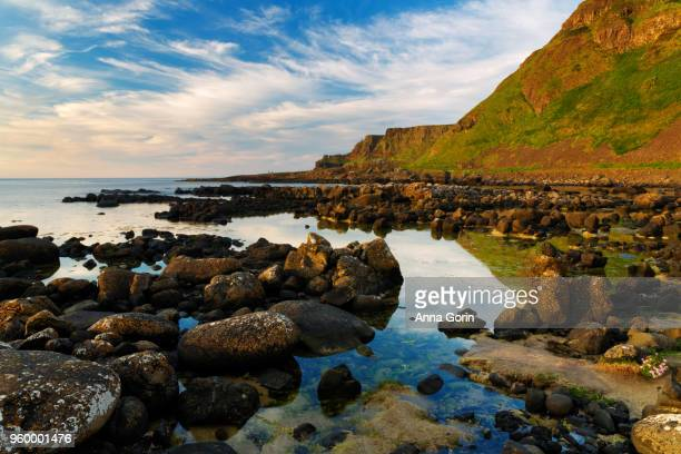 Mountains and rocks reflected in still waters along path leading to Giant's Causeway in Northern Ireland
