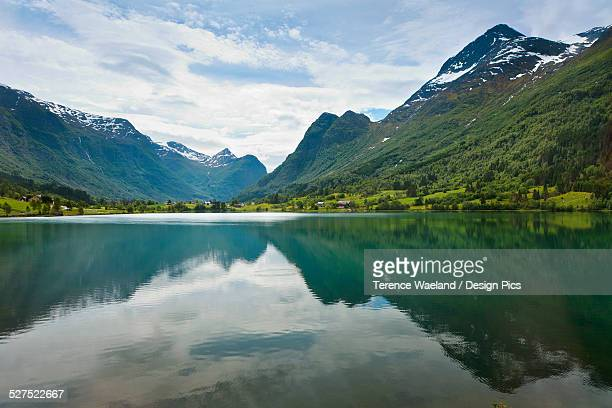 mountains and sky reflected in the tranquil water surrounded by mountains - terence waeland stock pictures, royalty-free photos & images