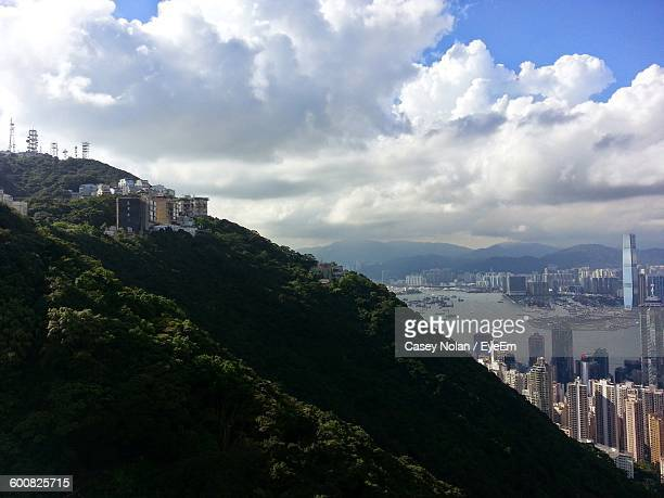 mountains by buildings against cloudy sky - casey nolan stock pictures, royalty-free photos & images