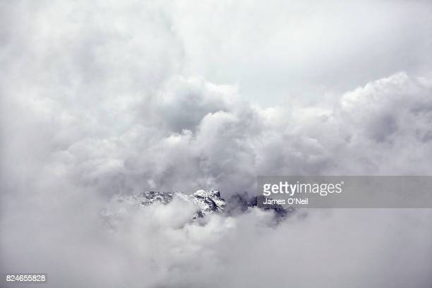 mountains emerging from stormy cloud - appearance stock pictures, royalty-free photos & images