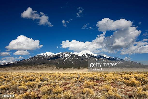 mountains looming over dry plains - thinkstock foto e immagini stock