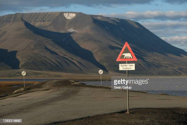Mountains nearly devoid of snow stand behind a road and a polar bear warning sign during a summer heat wave on Svalbard archipelago on July 29 2020...
