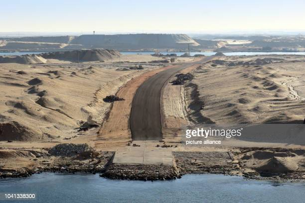 Mountains of sand rise up along the river bank of the Suez Canal in Egypt, 10 November 2016. The shipping canal is being currently enlarged. Waiting...