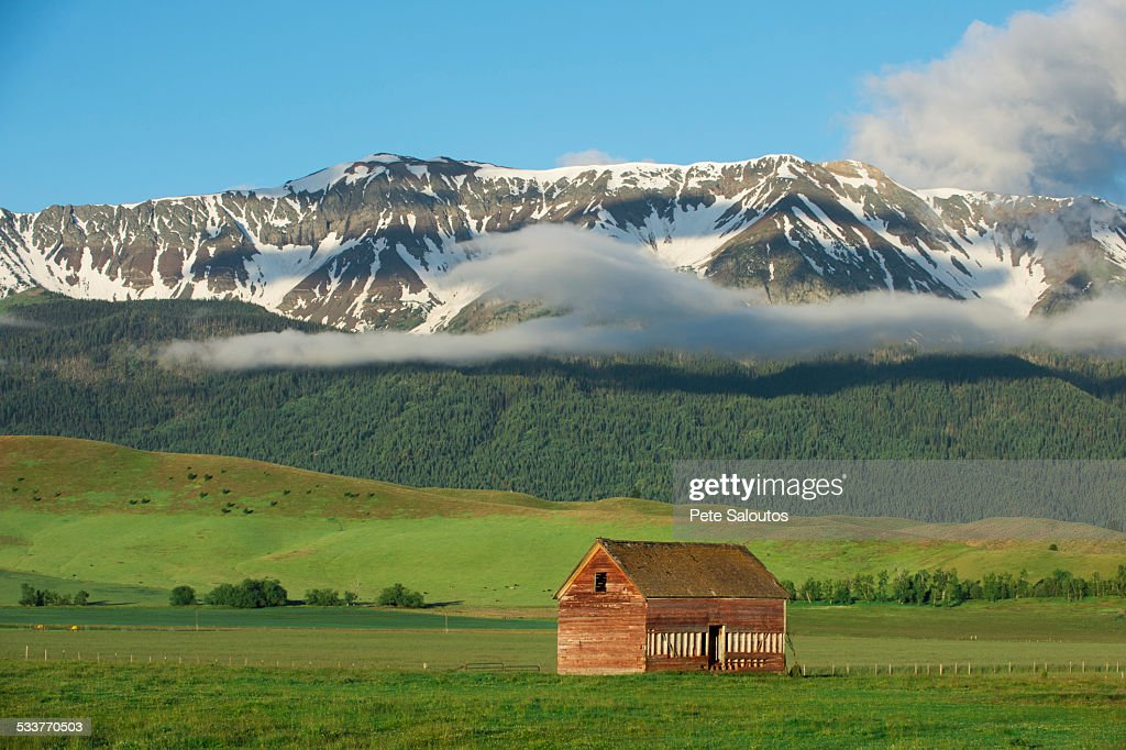 Mountains over barn in rural landscape : Foto stock